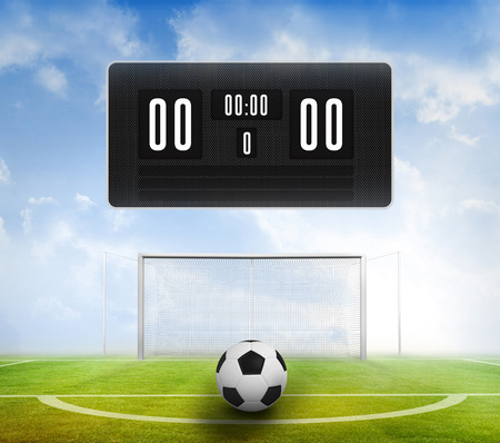 score under: Black scoreboard with no score and football against football pitch under blue sky