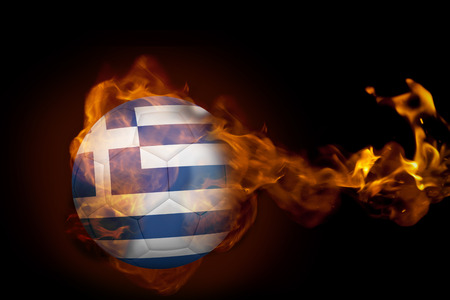 Composite image of fire surrounding greece ball against black photo