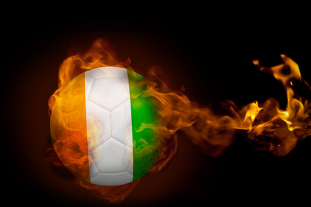 Composite image of fire surrounding ivory coast ball against black photo
