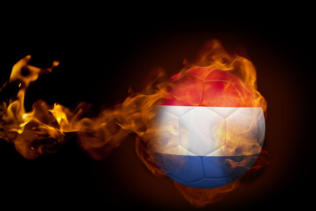 Composite image of fire surrounding holland ball against black photo