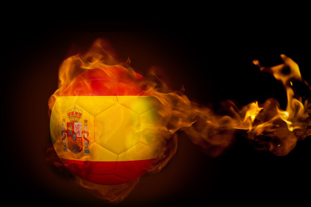 Composite image of fire surrounding spain ball against black photo