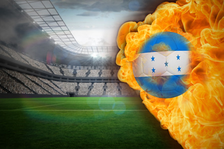 Composite image of fire surrounding honduras flag football against large football stadium with lights photo