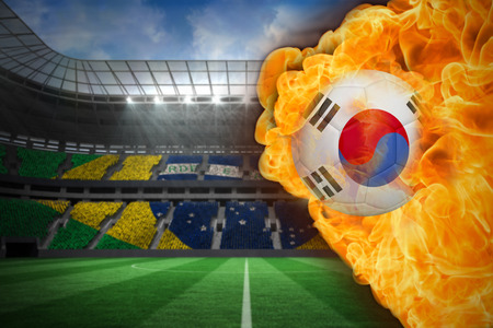Composite image of fire surrounding korea republic flag football against large football stadium with brasilian fans photo