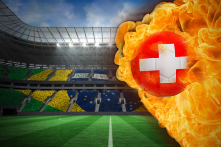 Composite image of fire surrounding switzerland flag football against large football stadium with brasilian fans photo