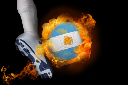 Football player kicking flaming argentina flag ball against black photo