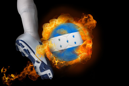 Football player kicking flaming honduras flag ball against black photo