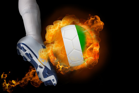 Football player kicking flaming ivory coast ball against black photo