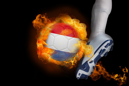 Football player kicking flaming netherlands ball against black photo