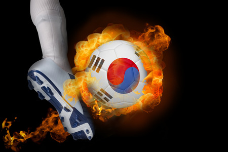 Football player kicking flaming korea republic ball against black photo
