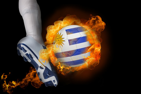 Football player kicking flaming uruguay ball against black photo