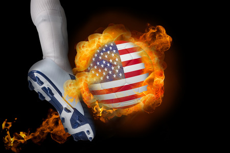 Football player kicking flaming usa ball against black photo