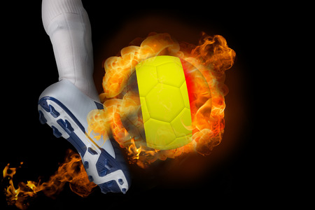 Football player kicking flaming belgium ball against black photo