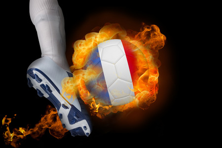 Football player kicking flaming france ball against black photo