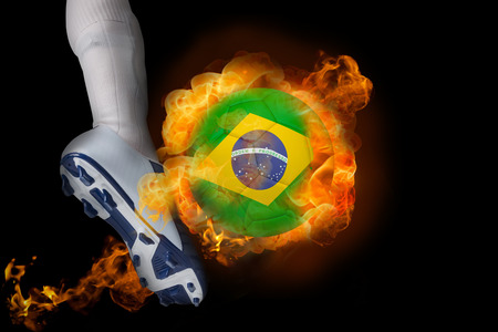 Football player kicking flaming brasil ball against black photo