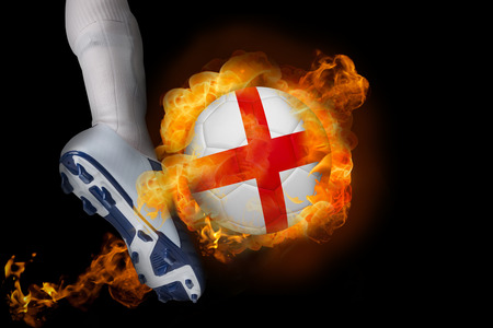 Football player kicking flaming england ball against black photo