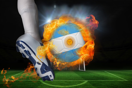 Football player kicking flaming argentina flag ball against football pitch and goal under spotlights photo