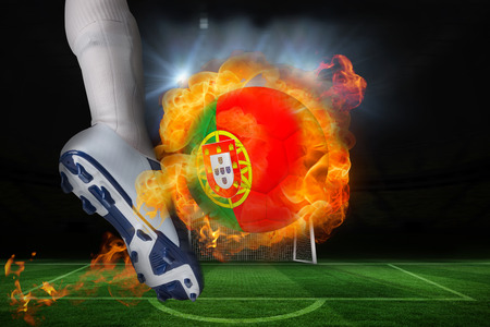 Football player kicking flaming portugal flag ball against football pitch and goal under spotlights photo