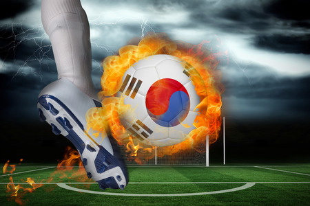 Football player kicking flaming south korea flag ball against football pitch under stormy sky photo