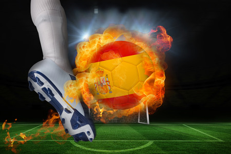 Football player kicking flaming spain flag ball against football pitch and goal under spotlights photo