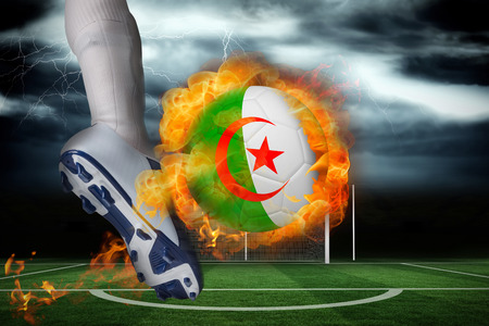 Football player kicking flaming algeria flag ball against football pitch under stormy sky photo
