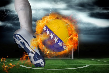 Football player kicking flaming bosnia flag ball against football pitch under stormy sky photo
