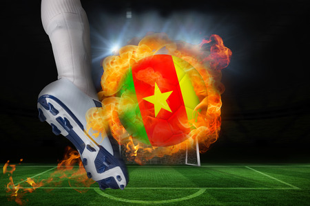 Football player kicking flaming cameroon flag ball against football pitch and goal under spotlights photo