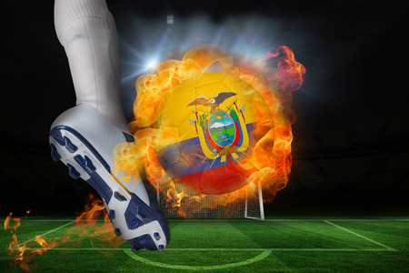 Football player kicking flaming ecuador flag ball against football pitch and goal under spotlights photo