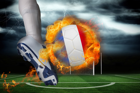 Football player kicking flaming france flag ball against football pitch under stormy sky photo