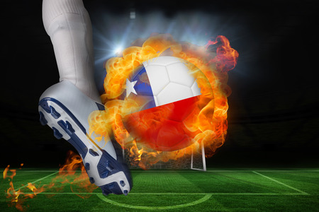 Football player kicking flaming chile flag ball against football pitch and goal under spotlights photo