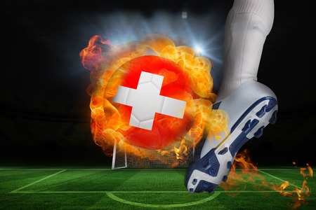 Football player kicking flaming swiss flag ball against football pitch and goal under spotlights photo