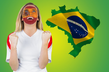 Excited spain fan in face paint cheering against green brazil outline with flag photo