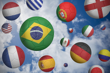 Footballs in various flag colours  against blue cloudy sky photo