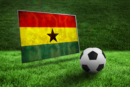 Black and white football on grass against ghana flag in grunge effect photo