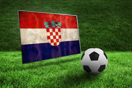 Black and white football on grass against croatia flag in grunge effect photo