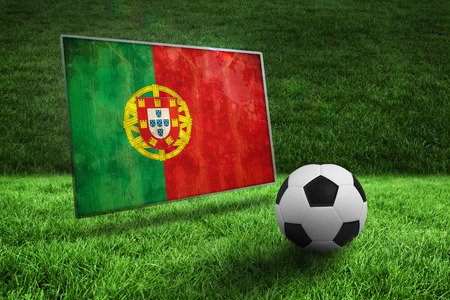Black and white football on grass against portugal flag in grunge effect photo