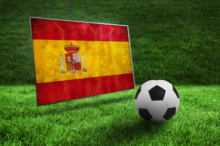 Black and white football on grass against spain flag in grunge effect photo