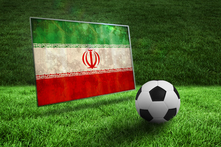 Black and white football on grass against iran flag in grunge effect photo