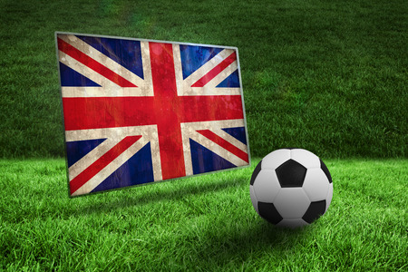 Black and white football on grass against union jack flag in grunge effect photo