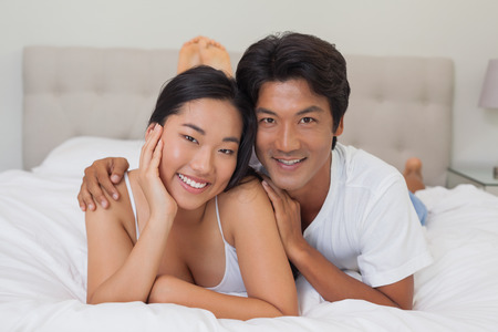 Happy couple lying on bed at home in bedroom photo