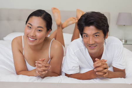 Happy couple lying on bed together at home in bedroom photo