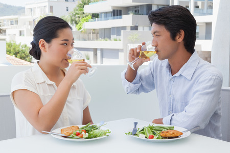 Happy couple having a meal together with white wine outside on a balcony photo