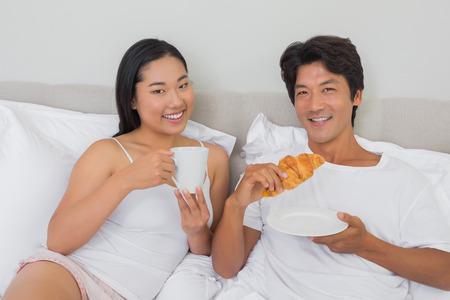 Happy couple having breakfast in bed at home in bedroom photo