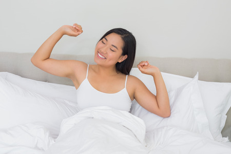 rested: Smiling woman lying in bed stretching in the morning at home in bedroom Stock Photo
