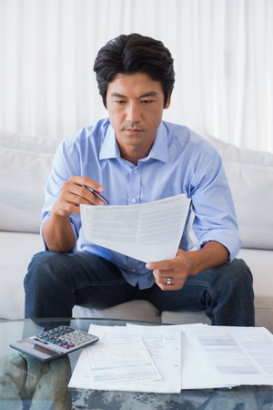 figuring: Man sitting on couch working out his finances at home in the living room Stock Photo