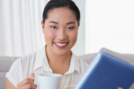Smiling woman sitting on couch using tablet pc having coffee at home in the living room photo