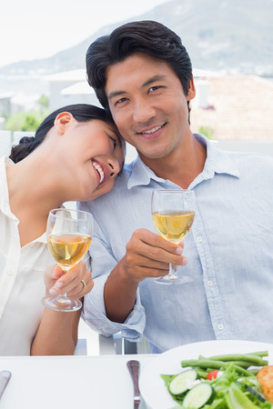 Happy couple having white wine with a meal outside on a balcony photo