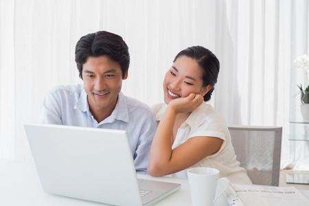 Happy couple using laptop together at home in the living room photo