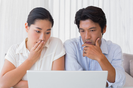 Worried couple using laptop together at home in the living room photo