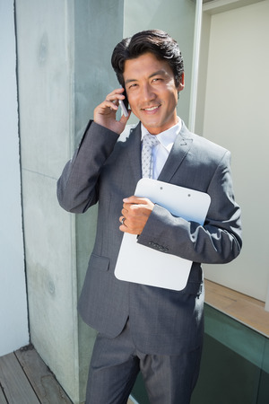 letting: Confident estate agent standing at front door on the phone outside a house