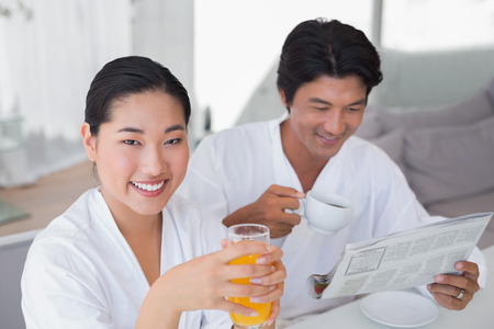 Couple in bathrobes spending the morning together at home in the living room photo